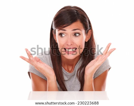 Headshot portrait of surprised latin woman with error hands looking to her right on isolated white background - copyspace - stock photo