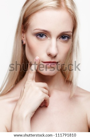 headshot portrait of young beautiful blonde woman placing finger on her cheek near leeps