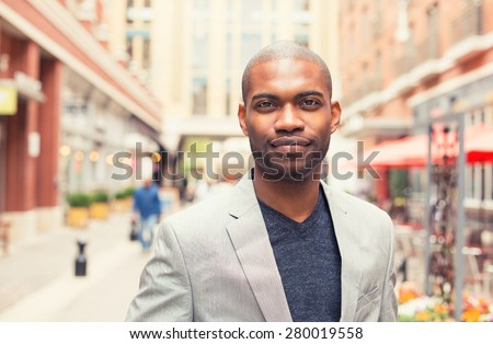 Headshot portrait of young man smiling isolated on outside outdoors background. - stock photo