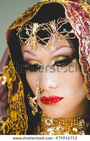 Headshot woman dressed in traditional hindu clothing, heavily decorated in gold and elegant veil, posing artistically for camera, hindusim dancer concept