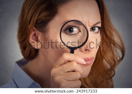 Headshot woman investigator looking through magnifying glass