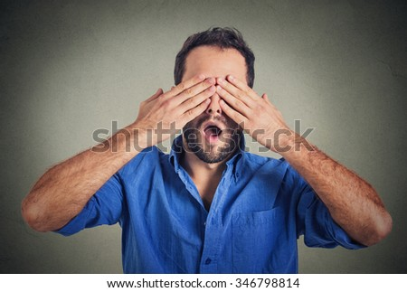 Headshot young scared man covering eyes with hands wide open mouth isolated on grey wall background. Human emotions face expressions feelings reaction perception. See no evil concept  - stock photo