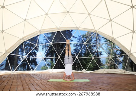 Headstand in beautiful yoga place. - stock photo