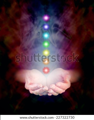 Healer's hands emerging from black background, cupped with seven chakra vortexes hovering above and misty burgundy colored energy formation