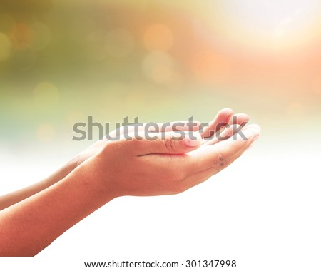 Healing Amazing Light - Human healer with hands open palm up surrounded by a ray white light. Praying hand over blurred sunset background. - stock photo