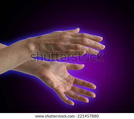 Healing Hands Aura - Healer's outstretched hands sensing energy on a black background showing electromagnetic energy field - stock photo