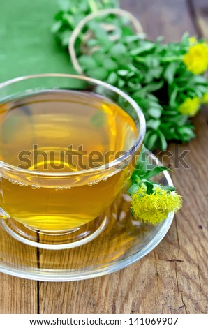 Healing herbal tea in glass cup with flowers Rhodiola rosea, green cloth on a background of wooden boards