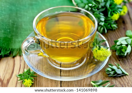 Healing herbal tea in glass cup with flowers Rhodiola rosea, green cloth on a wooden board
