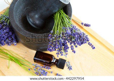 Healing herbs, black mortar with lavender flowers, bottle with oil, herbal medicine - stock photo