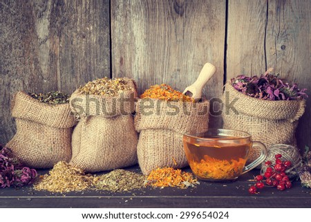 Healing herbs in hessian bags and healthy tea cup, herbal medicine.Retro styled. - stock photo