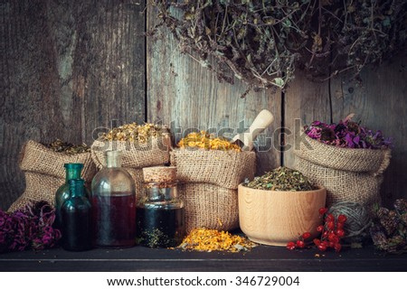 Healing herbs in hessian bags, mortar and bottles of tincture or oil, herbal medicine. - stock photo