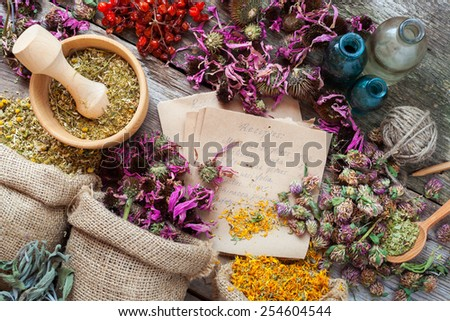 Healing herbs in hessian bags, wooden mortar, bottles with tincture, herbal medicine. Top view. - stock photo