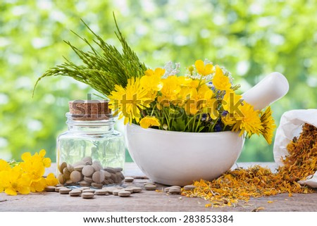 Healing herbs in mortar and bottle of pills on rustic table, herbal medicine. - stock photo