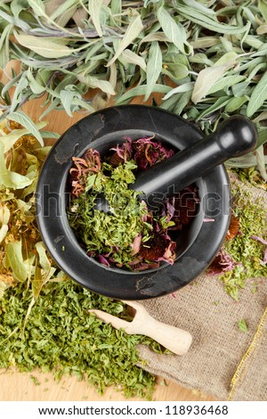healing herbs on wooden table, mortar and pestle, herbal medicine, top view - stock photo