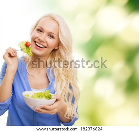 healt, dieting and happiness concept - smiling young woman with green salad - stock photo
