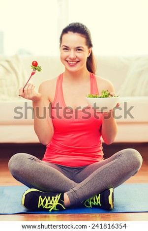 healt, dieting, home and happiness concept - smiling sporty teenage girl with green salad at home - stock photo