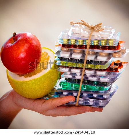 Health and balanced diet concept. Choice between two sources of vitamins - pills or fruits. Closeup female hand holding stack of drugs apple and grapefruit - stock photo