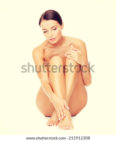 health and beauty concept - beautiful naked woman touching her legs - stock photo