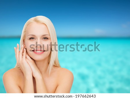 health and beauty concept - face and hands of happy woman