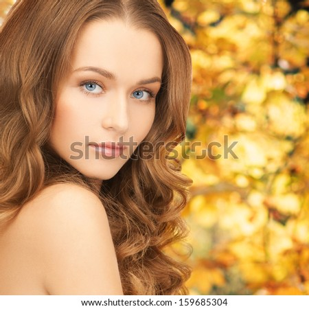 health and beauty concept - face of beautiful woman with long hair over yellow autumn leaves background - stock photo
