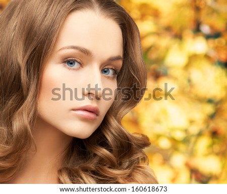 health and beauty concept - face of beautiful woman with long hair over yellow autumn leaves background