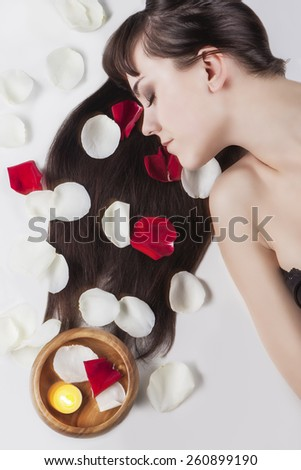 Health and Beauty Concept: Portrait of Relaxing Caucasian Female With Soft Silky Skin and Long Dark Hair.Rose Leafs and Wooden Bowl Are Used.Vertical Image Composition - stock photo