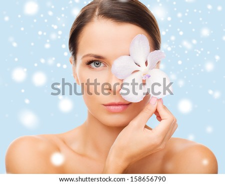 health and beauty concept - relaxed woman with orchid flower over eye - stock photo