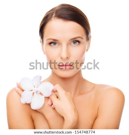 health and beauty concept - relaxed woman with orhid flower - stock photo