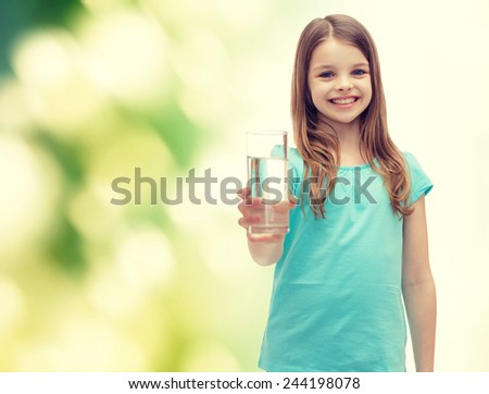 health and beauty concept - smiling little girl giving glass of water - stock photo