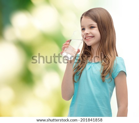 health and beauty concept - smiling little girl with glass of water - stock photo