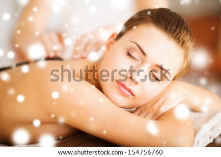 health and beauty concept - woman in spa salon with hot stones - stock photo