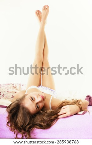 Health and beauty concept. Young lovely blonde woman long curly hair relaxing on her bed at morning - stock photo