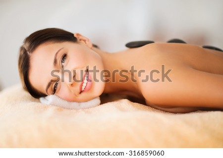 health and beauty, resort and relaxation concept - beautiful woman in spa salon with hot stones - stock photo