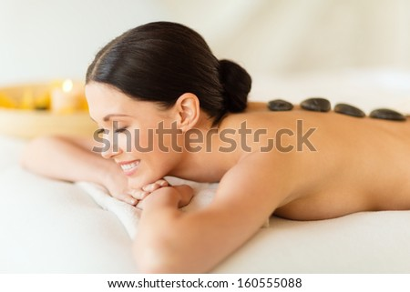 health and beauty, resort and relaxation concept - woman in spa salon with hot stones - stock photo