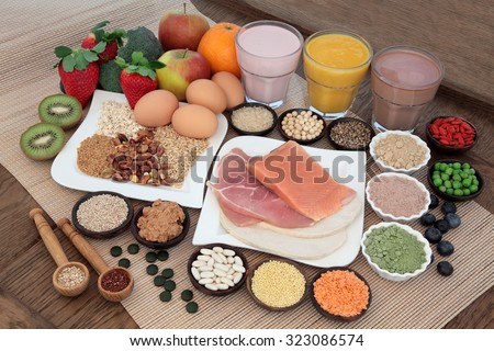 Health and body building food with fish and meat, supplement powders, vitamin tablets, pulses, nuts, vegetables, fruit and high protein and juice smoothie shakes. - stock photo