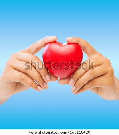 health and charity concept - close up of woman hands holding heart - stock photo
