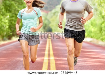 Health and fitness running. Runners on run training during fitness workout outside on road. People jogging together living healthy active lifestyle outside in summer. Midsection of woman and man. - stock photo
