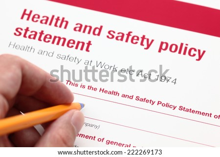 Health and safety policy statement and hand with ballpoint pen.