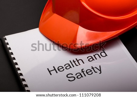 Health and safety register with helmet - stock photo