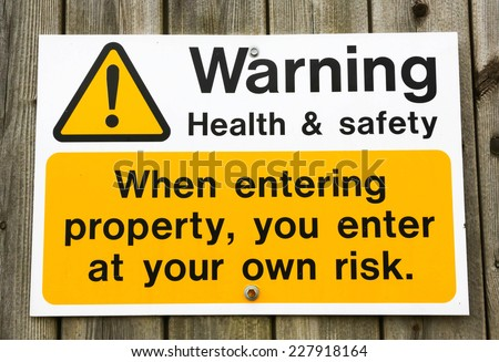 Health and Safety warning sign advising that you enter a building at your own risk. - stock photo