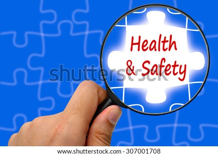 Health and safety word. Magnifier and puzzles.