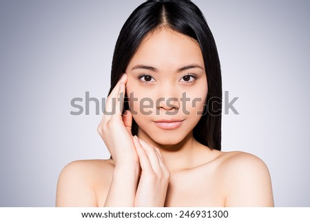 Health and wellness. Portrait of beautiful young and shirtless Asian woman touching her face while standing against grey background   - stock photo