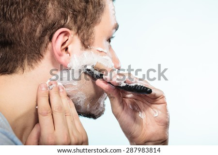 Health beauty and skin care concept. Closeup young bearded man with foam on face shaving with razor on blue background.