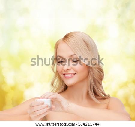 health, beauty and spa concept - beautiful woman applying cream - stock photo