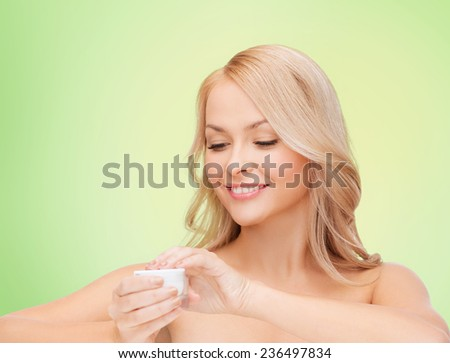health, beauty and spa concept - smiling young woman opening cream over green background - stock photo
