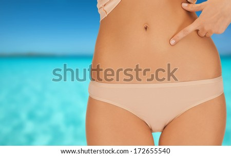 health, beauty and vacation concept - close up of woman pointing at her abs - stock photo