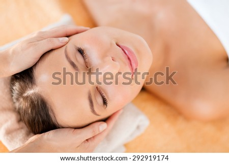 health, beauty, resort and relaxation concept - beautiful woman in spa salon getting face treatment