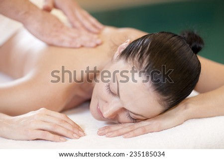 health, beauty, resort and relaxation concept - beautiful woman in spa salon getting massage - stock photo