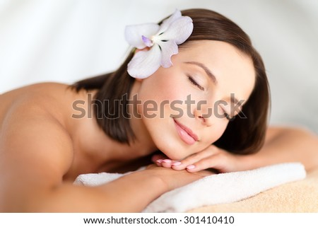 health, beauty, resort and relaxation concept - beautiful woman with flower in her hair in spa salon lying on the massage desk - stock photo