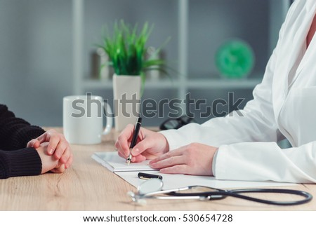 Health care and medical concept - close up of female patient and doctor hands meeting in hospital office and making appointment for medical exam